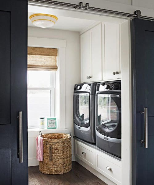 white laundry room cabinetry raised drawer storage sliding doors woven basket.